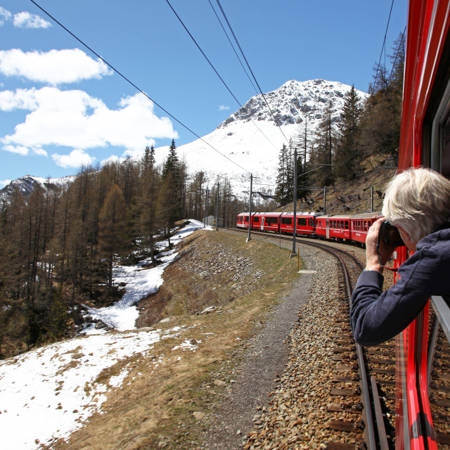 """""""A photographer taking a picture of the view of the Swiss Alps from the Bernina Express train"""" stock image"""