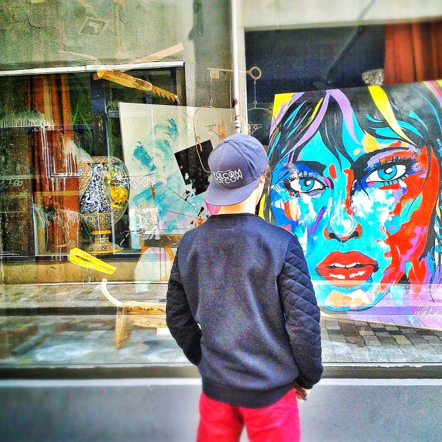 """""""Boy looking at artwork in store window"""" stock image"""