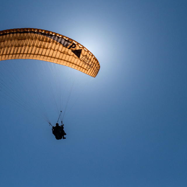 """""""Paraglider flying in front of the Sun"""" stock image"""