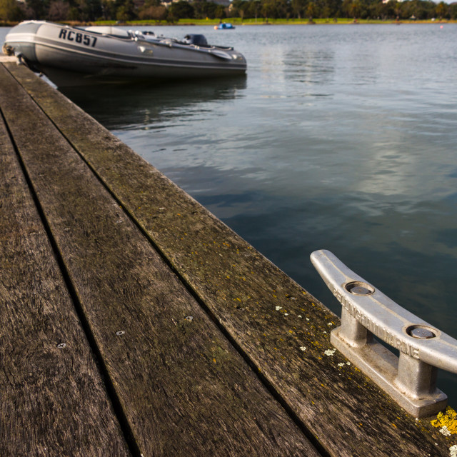 """""""Mooring Bollard with Rubber Dinghy in the Background"""" stock image"""