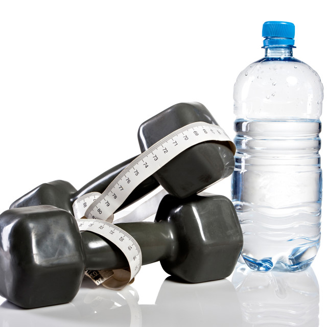 """Weights, botte of water and measure tape"" stock image"
