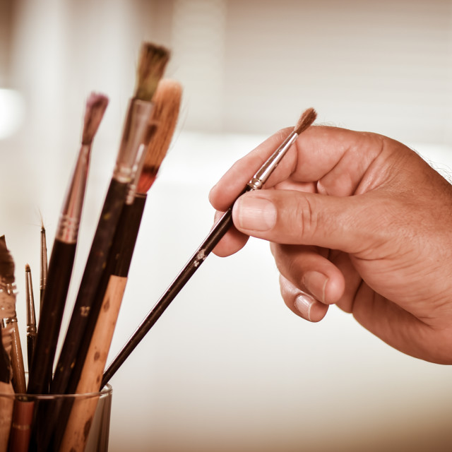 """""""Painter's hand taking a brush in a pot"""" stock image"""