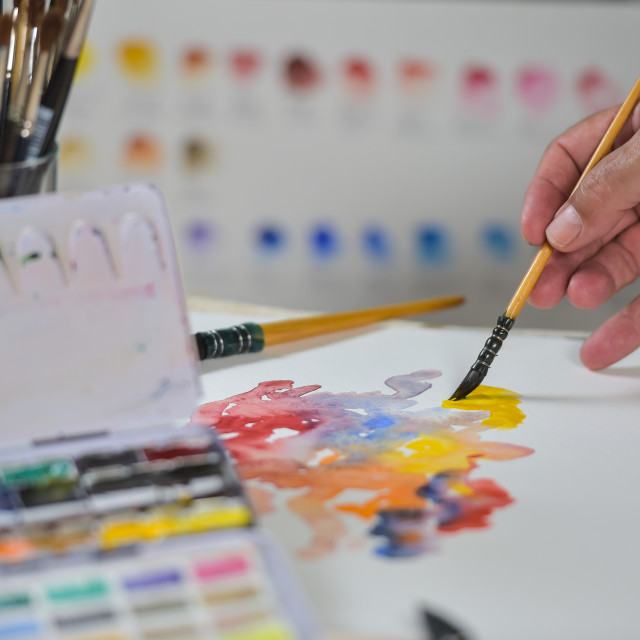 """""""Artist's hand applying paint gouache on the drawing sheet"""" stock image"""