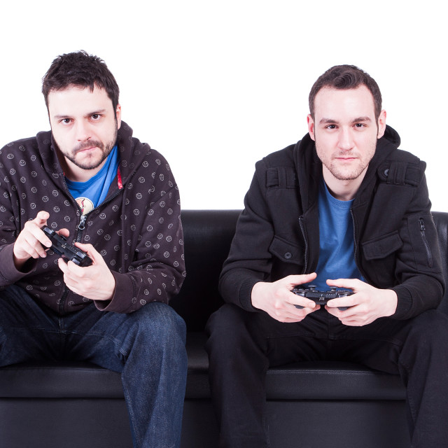 """Two guys playng video games and sitting on a sofa"" stock image"
