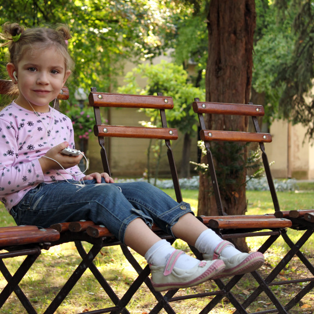"""""""little girl sitting in the park and listen music on phone"""" stock image"""