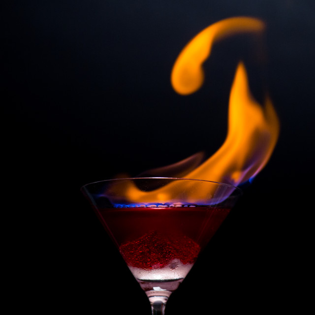 """""""Fire blowing out of martini glass/close-up with black background"""" stock image"""
