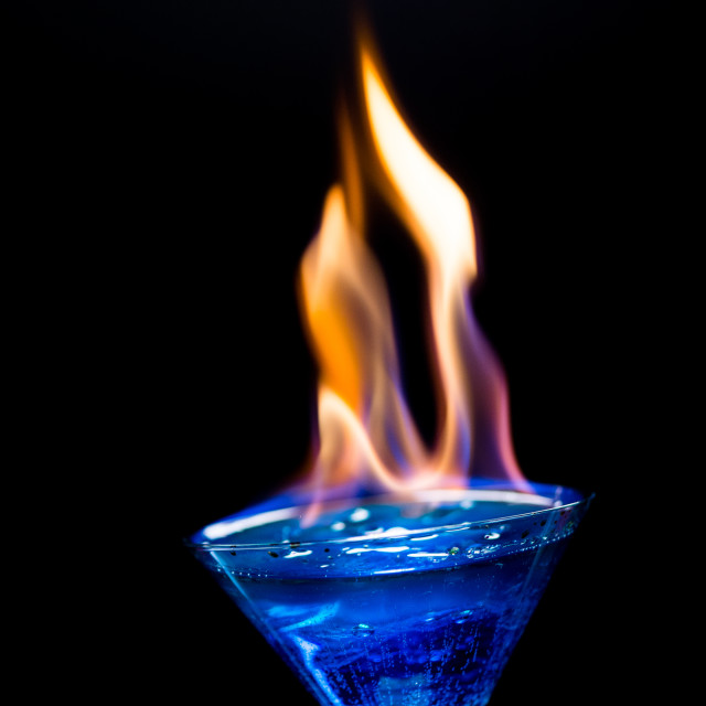 """""""Fire blowing out of blue lagoon glass/close-up with black backgr"""" stock image"""