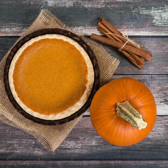 """Pumpkin pie with pumpkin and cinnamon sticks against rustic tabl"" stock image"