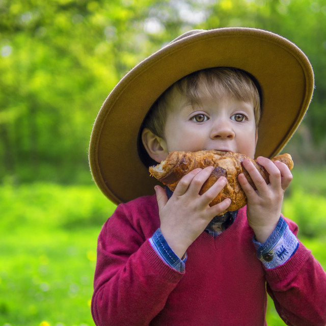 """Cute boy eating a croissant"" stock image"