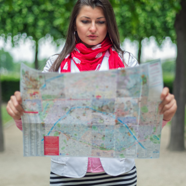 """""""Young woman looking on the map at the city park Paris, France"""" stock image"""