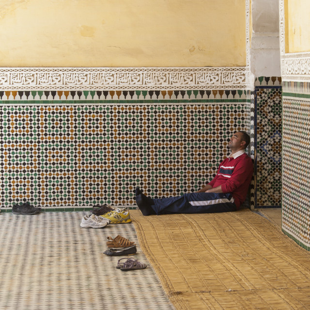 """Man resting against wall of mosque"" stock image"