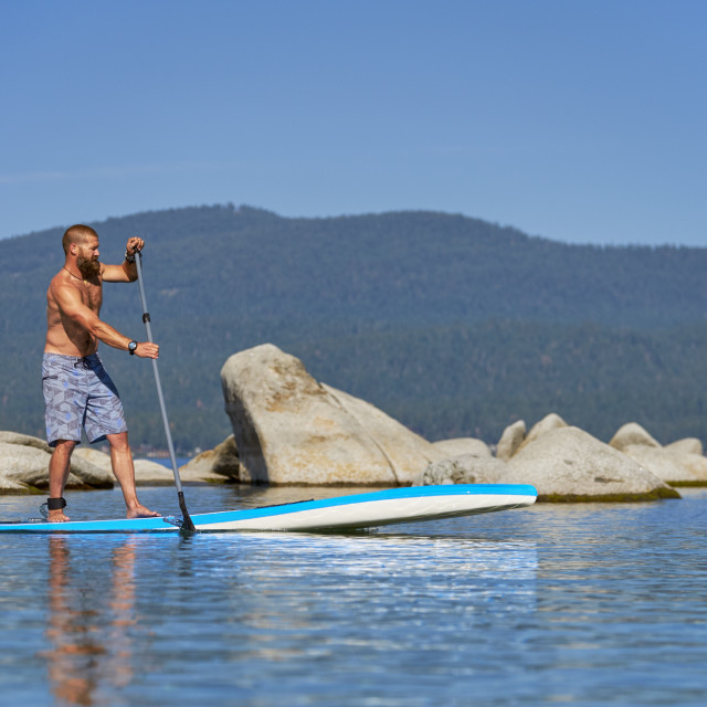 """""""A Young Man with a Long Beard on a Paddle Board on Lake Tahoe."""" stock image"""