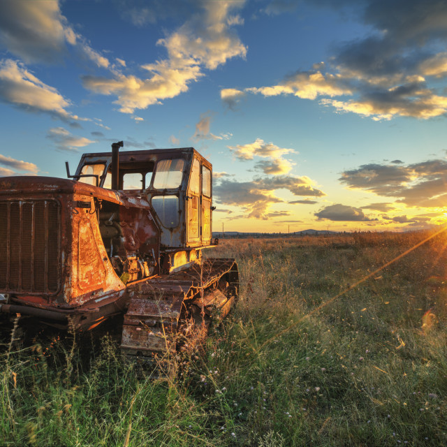 """Old rusty tractor in a field on sunset"" stock image"