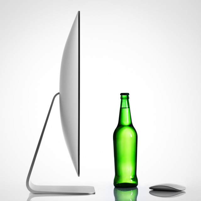 """""""Isolated computer and beer bottle on a white background"""" stock image"""