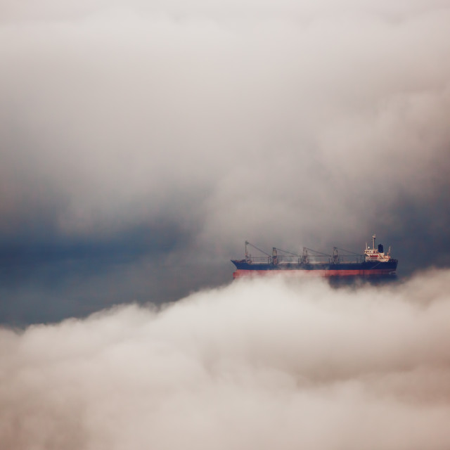 """Cargo ship sailing in water of clouds"" stock image"