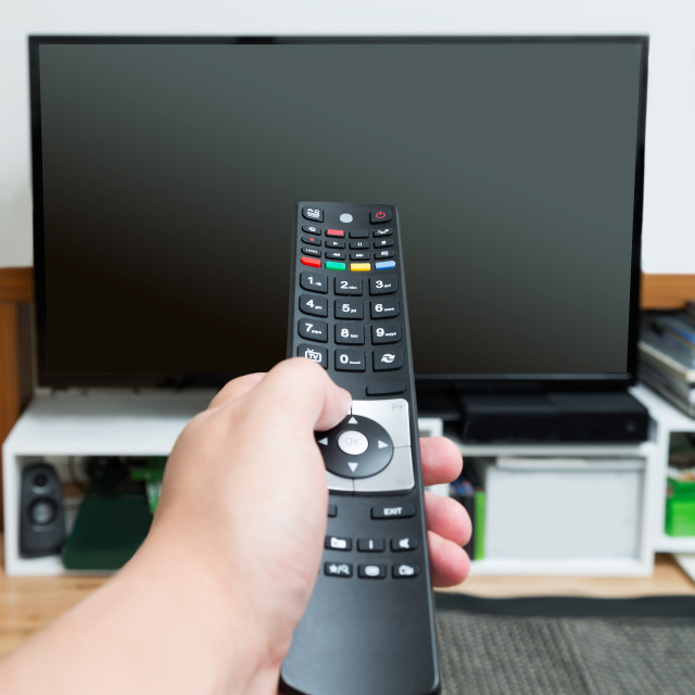 """Hand holding and pointing remote control"" stock image"