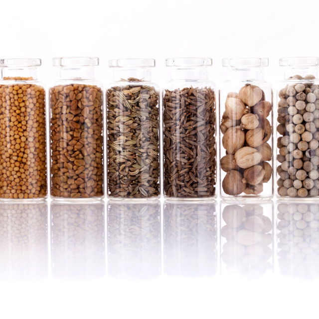 """Assorted of spice bottles condiment black pepper ,white pepper, black mustard,white mustard,fenugreek,cumin and fennel seeds isolated on white background."" stock image"