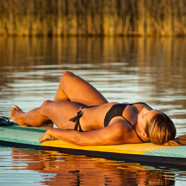 """Woman Relaxing On A Paddle Board"" stock image"