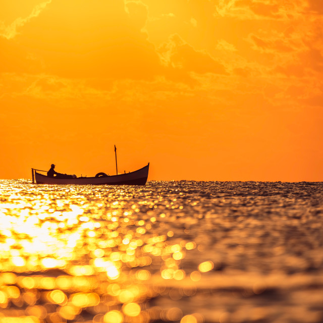 """Fisherman sailling with his boat on beautiful sunrise over the sea"" stock image"