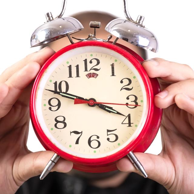 """Humans hand holding alarm clock"" stock image"
