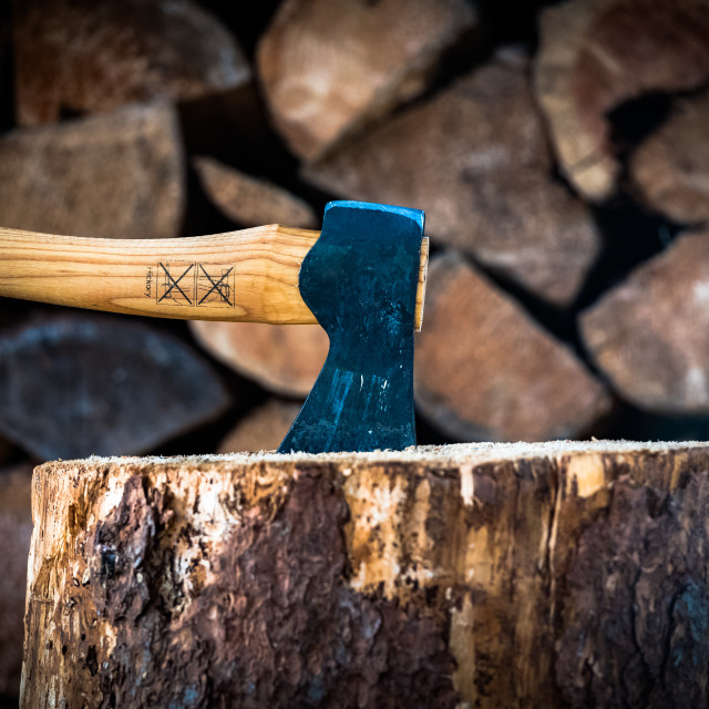 """Axe closeup, with a stacked firewood background"" stock image"