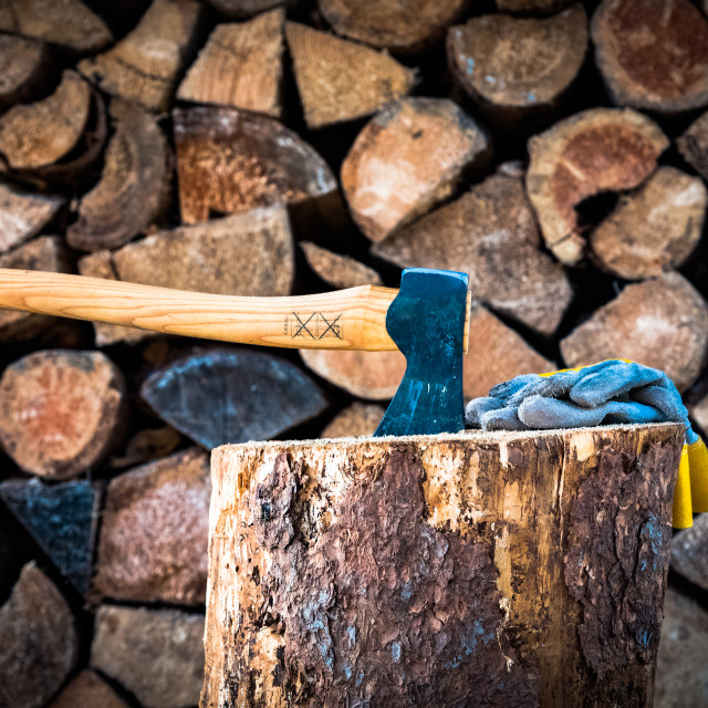 """Axe (with work gloves), with a stacked firewood background"" stock image"