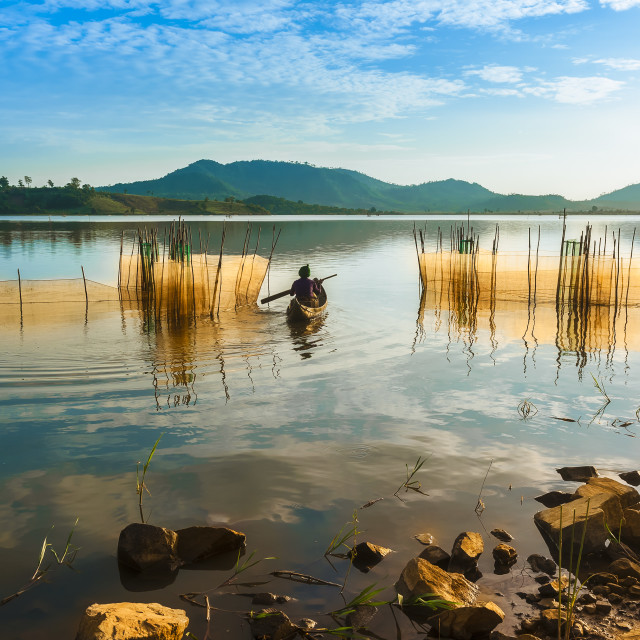 """Rade minority woman rowing her dugout canoe to visit the fishing net"" stock image"