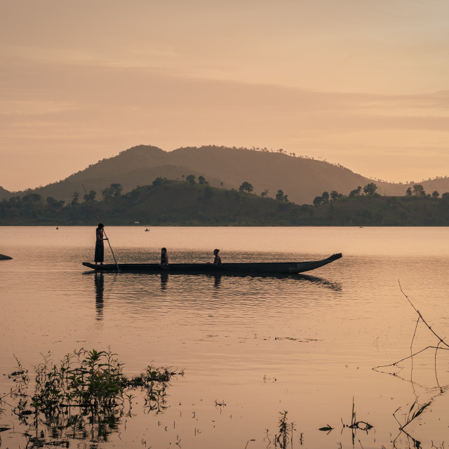 """Rade minority women rowing their dugout canoe at sunrise"" stock image"