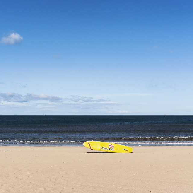 """Lifeguard surf board on beach with flags"" stock image"