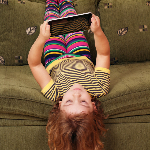 """little girl lying upside down on bed and play with tablet"" stock image"