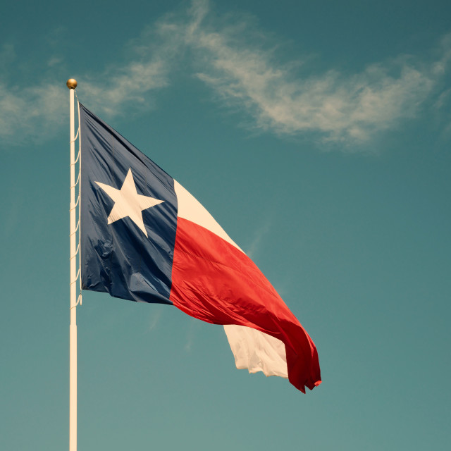 """State flag of Texas against blue sky"" stock image"
