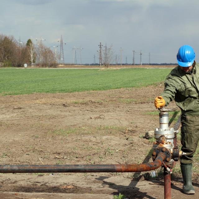 """oil worker open pipeline valve"" stock image"