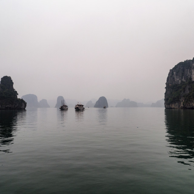 """Boats in Misty Halong Bay Rock Islands, Vietnam"" stock image"