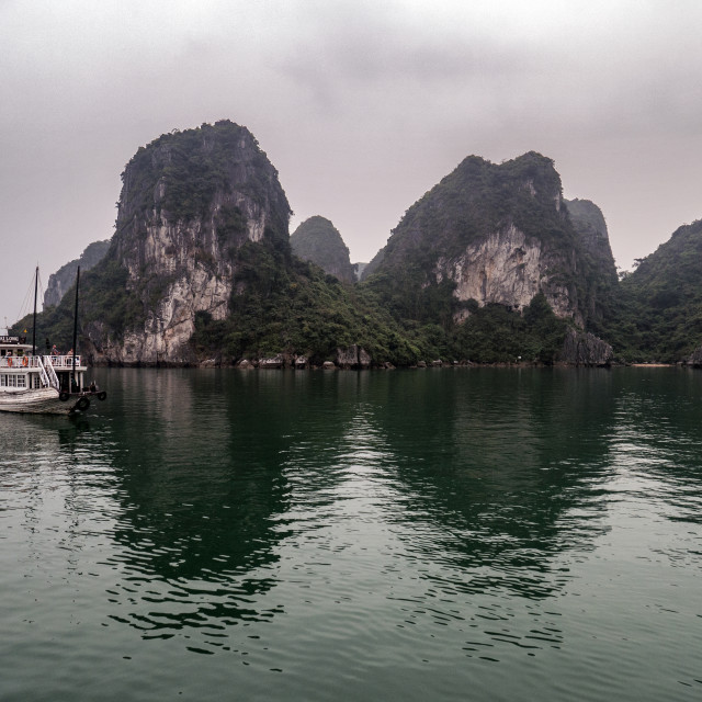 """Boat in Misty Halong Bay Rock Islands, Vietnam"" stock image"