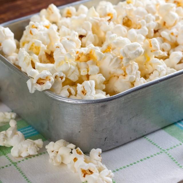 """Aluminum plate full of salty popcorn on towel"" stock image"