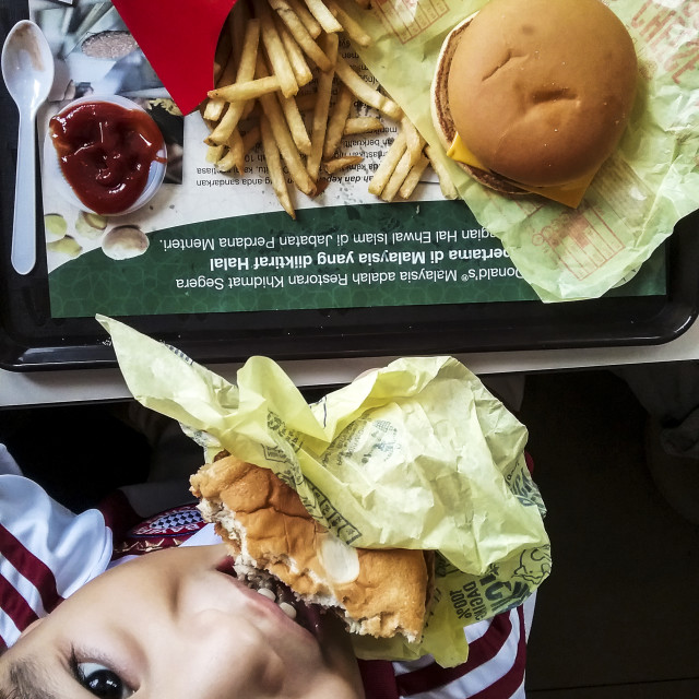 """Young Kid Eating Mcdonald Burger"" stock image"