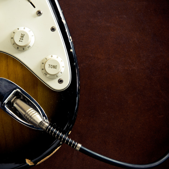 """Guitar body part plugged cable detail"" stock image"