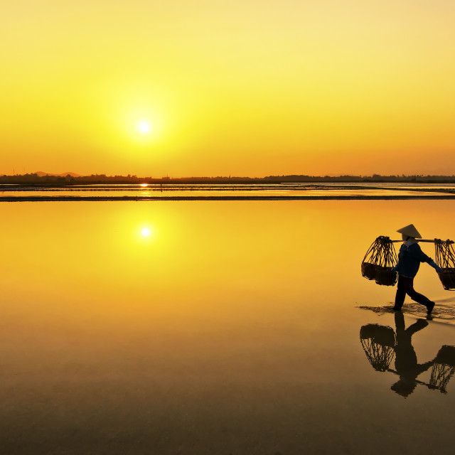 """Farmer going home after a hard working day in Hon Khoi salt field, Nha Trang, Vietnam"" stock image"