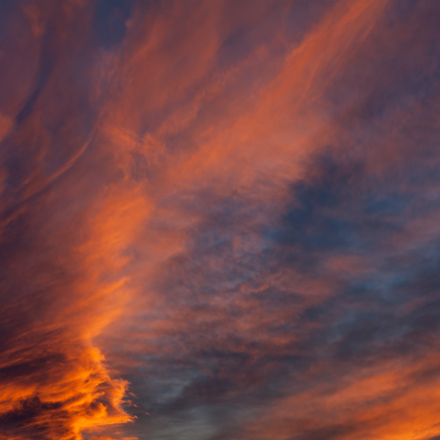 """Brooding orange sunset clouds"" stock image"
