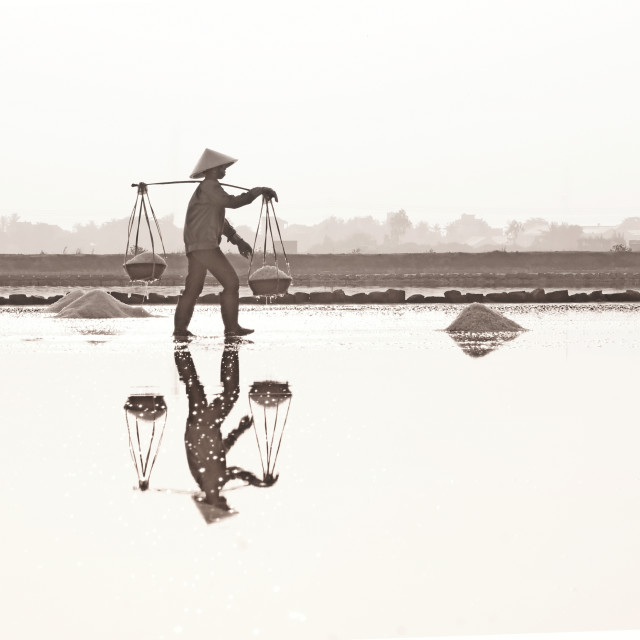 """Farmer harvests salt in Hon Khoi salt field, Nha Trang, Vietnam"" stock image"