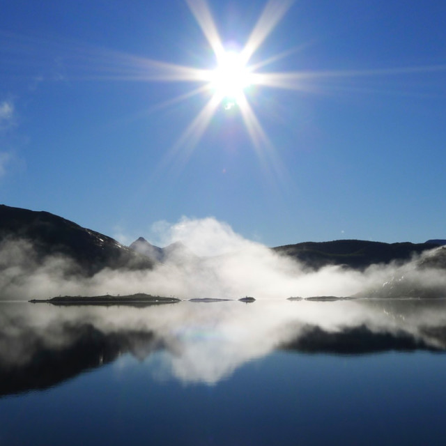 """Sun over cloudy lake"" stock image"