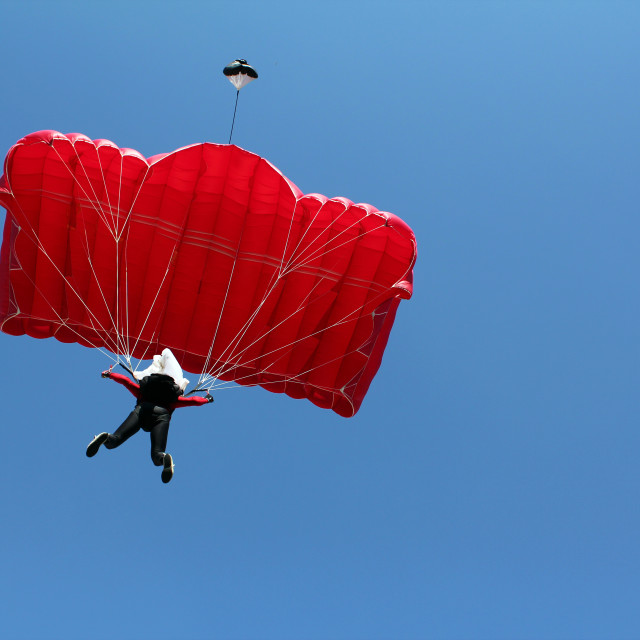 """parachutist with red parachute on blue sky"" stock image"
