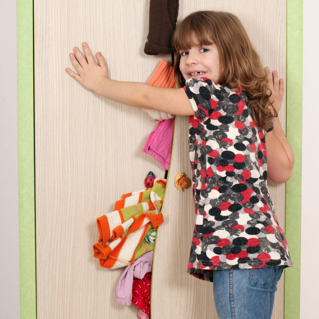 """""""upset little girl trying to close the closet"""" stock image"""