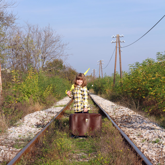 """""""little girl with suitcase and umbrella standing on railroad"""" stock image"""