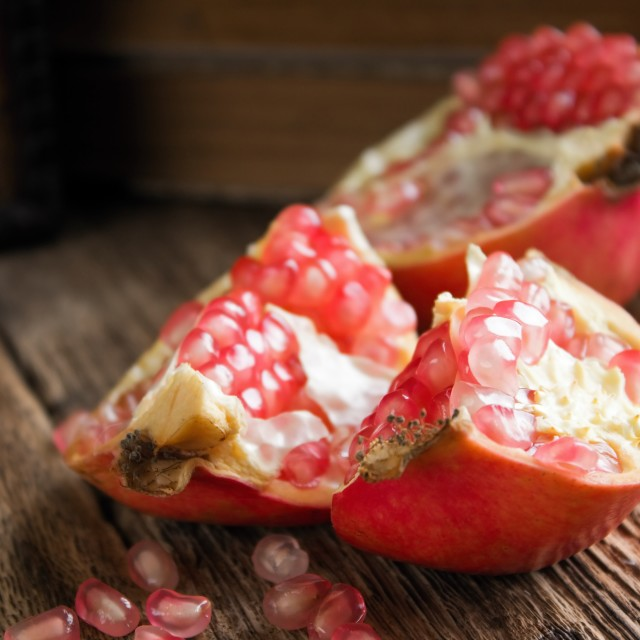 """""""Single pomegranate divided to three parts on table"""" stock image"""