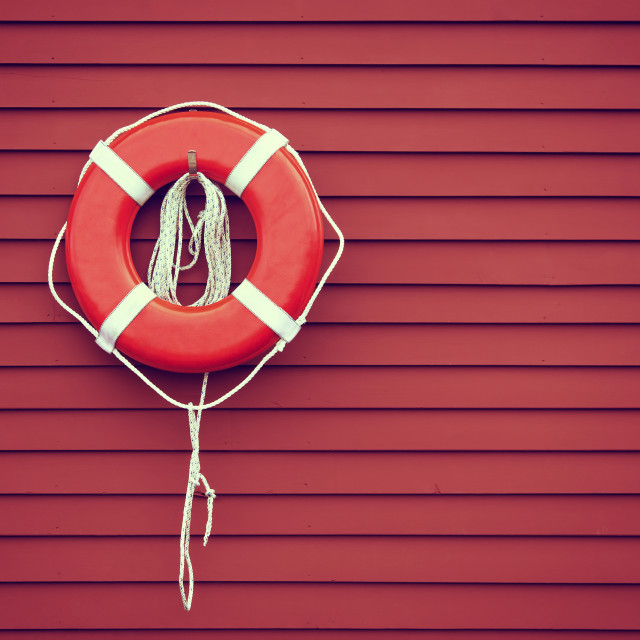 """Ring buoy on red wooden wall"" stock image"