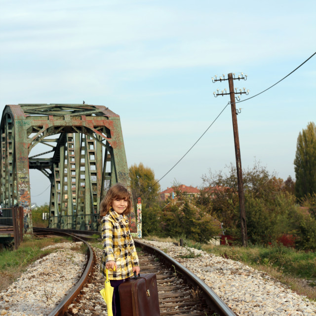 """""""little girl with umbrella and suitcase on railroad"""" stock image"""