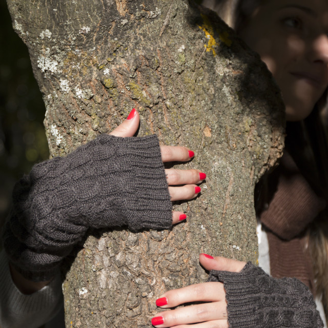 """""""Hands of a woman in gloves with nail polish hugging tree"""" stock image"""