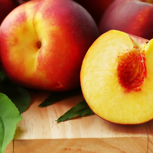 """sliced peaches and leaves on table"" stock image"
