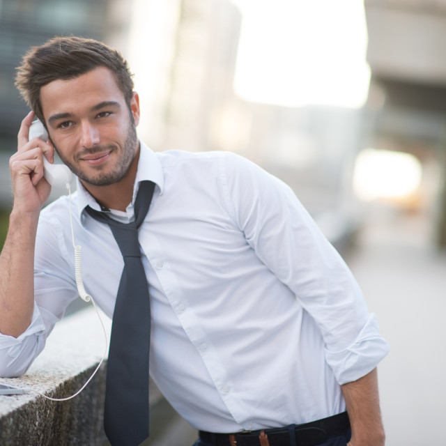 """""""A man using a cell phone with a funny headphone"""" stock image"""
